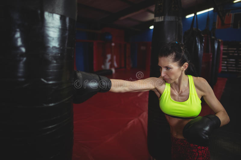 Praktiserande boxning för kvinnlig boxare med att stansa påsen arkivfoto
