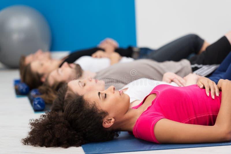 Praktiserande djup andning för aerobicsgrupp royaltyfri fotografi