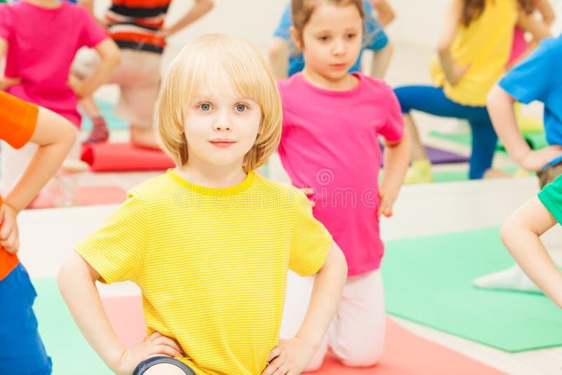 Praktiserande gymnastik för ungepojke i dagis arkivfoto