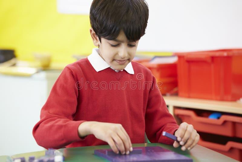 Praktiserande matematik för manlig elev på skrivbordet arkivfoton