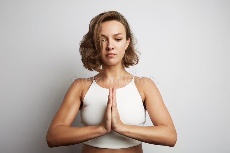 Praktiserande meditation för ung kvinna på kontoret, online-yogagrupper som tar en avbrottstid för en minut arkivbild