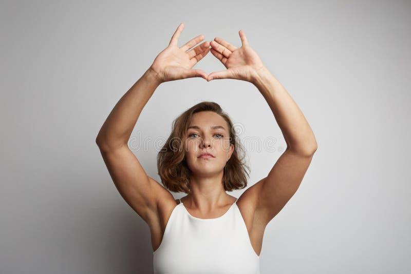 Praktiserande meditation för ung kvinna på kontoret, online-yogagrupper som tar en avbrottstid för en minut royaltyfri foto