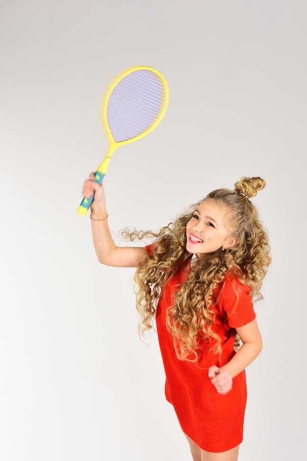 Praktiserande tennis F?rbereda sig till den stora leken liten flicka f?r blont h?r i r?d racket f?r kl?nningh?lltennis Kvinnligsp arkivfoton