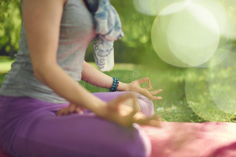 Praktiserande uppmärksam medvetenhet för fridfull och fridsam kvinna, genom att meditera i natur på solnedgången med bakgrundsbok royaltyfria bilder
