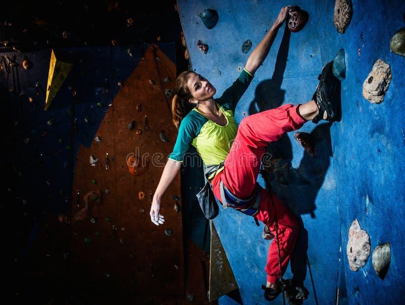 Praktiserande vagga-klättring för kvinna på en vaggavägg arkivbild