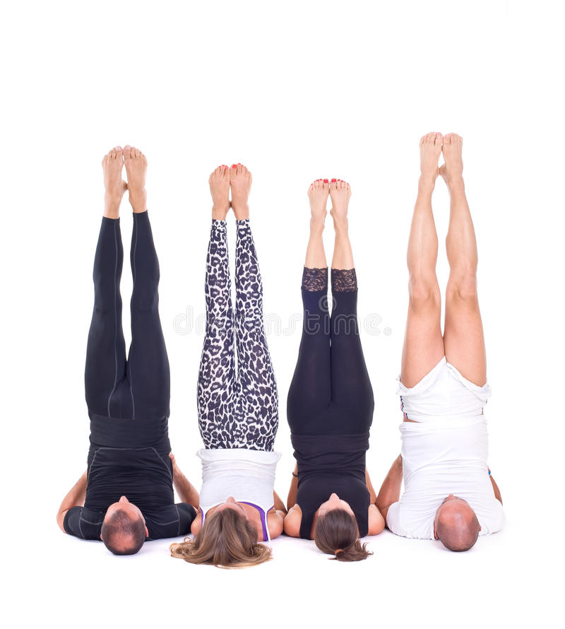 Praktiserande yoga övar i gruppen/Shoulderstand - Sarvangasana - Viparita Karani fotografering för bildbyråer