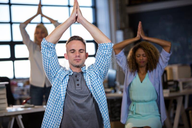 Praktiserande yoga för affärsman med coworkers arkivbilder