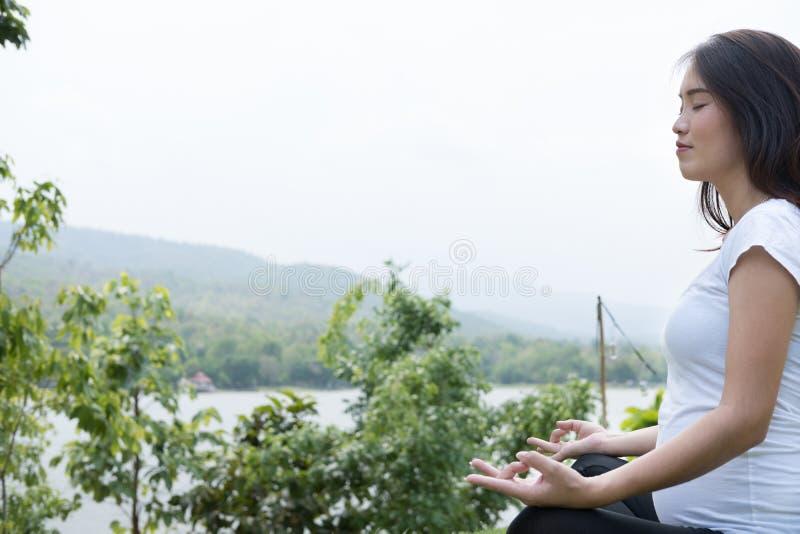 praktiserande yoga för asiatisk gravid kvinna, medan sitta i lotusblommaposi arkivbild