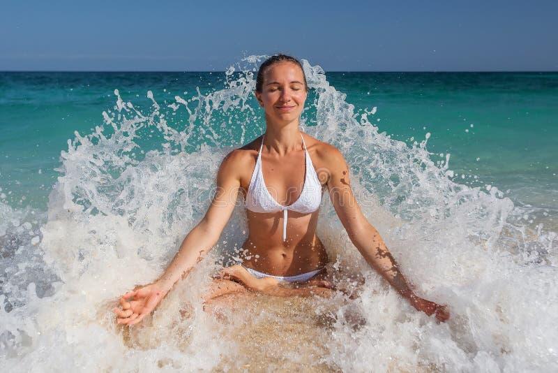 Praktiserande yoga för Caucasian kvinna på kusten arkivfoto
