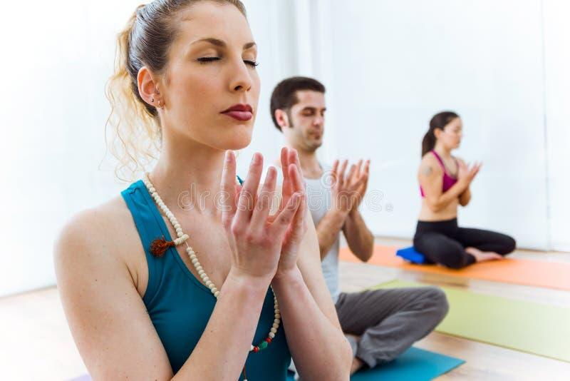 Praktiserande yoga för grupp människor hemma i lotusblommapositionen arkivbild