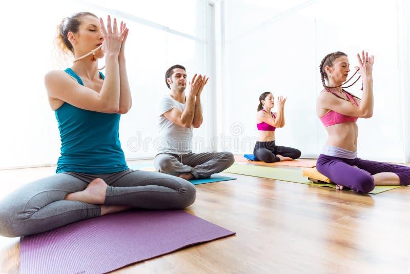 Praktiserande yoga för grupp människor hemma i lotusblommapositionen arkivbilder