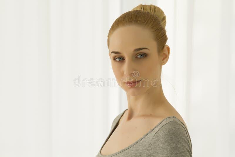Praktiserande yoga för härlig blond kvinna som hemma sträcker i den gråa bodysuiten, ståendeskott royaltyfria bilder