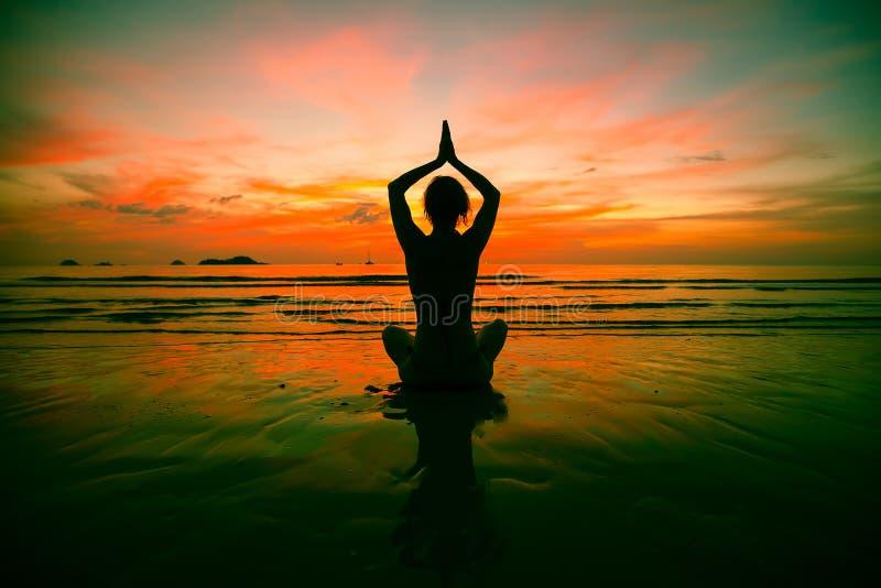 Praktiserande yoga för konturkvinna på stranden på den overkliga solnedgången arkivbilder