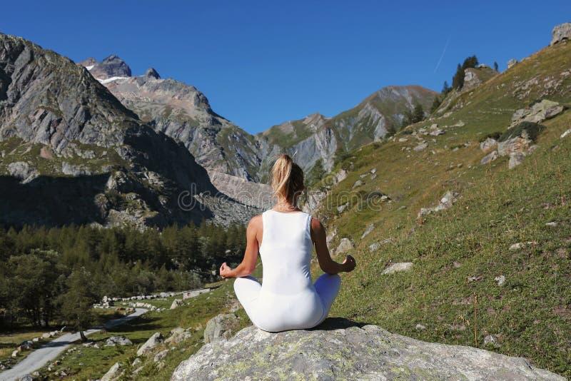 Praktiserande yoga för kvinna i lotusblommaposition arkivfoto