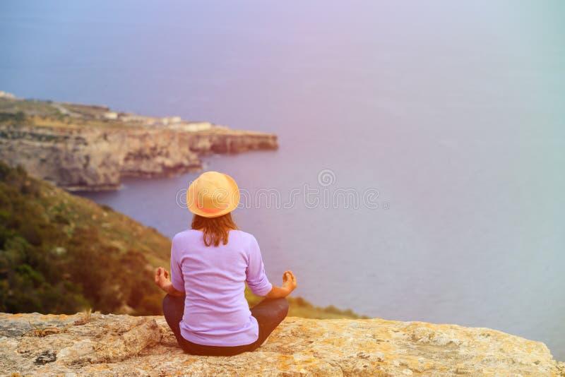 Praktiserande yoga för kvinna i sceniska berg royaltyfria foton
