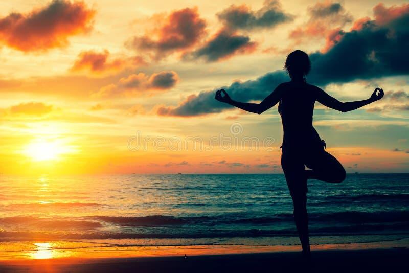 Praktiserande yoga för kvinna på havkusten under en magisk solnedgång silhouette royaltyfri bild