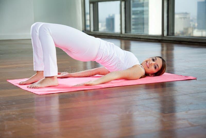Praktiserande yoga för kvinna på mattt royaltyfri foto