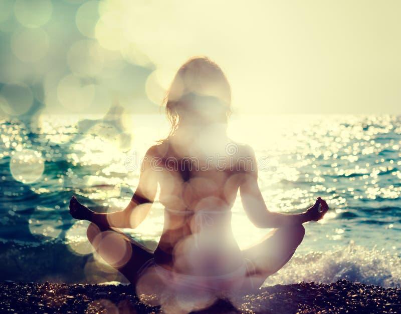 Praktiserande yoga för kvinna vid havet royaltyfri fotografi