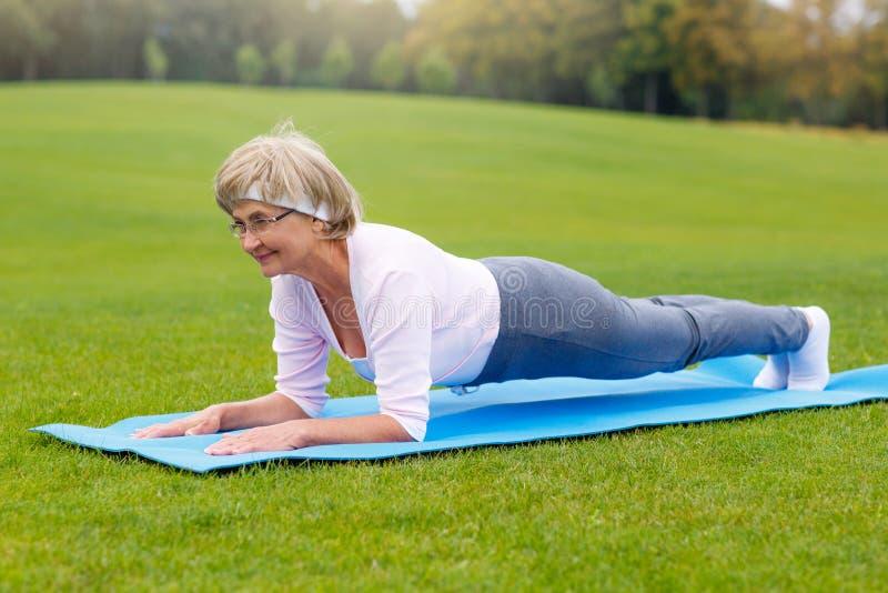 Praktiserande yoga för mogen kvinna i parkera royaltyfria foton