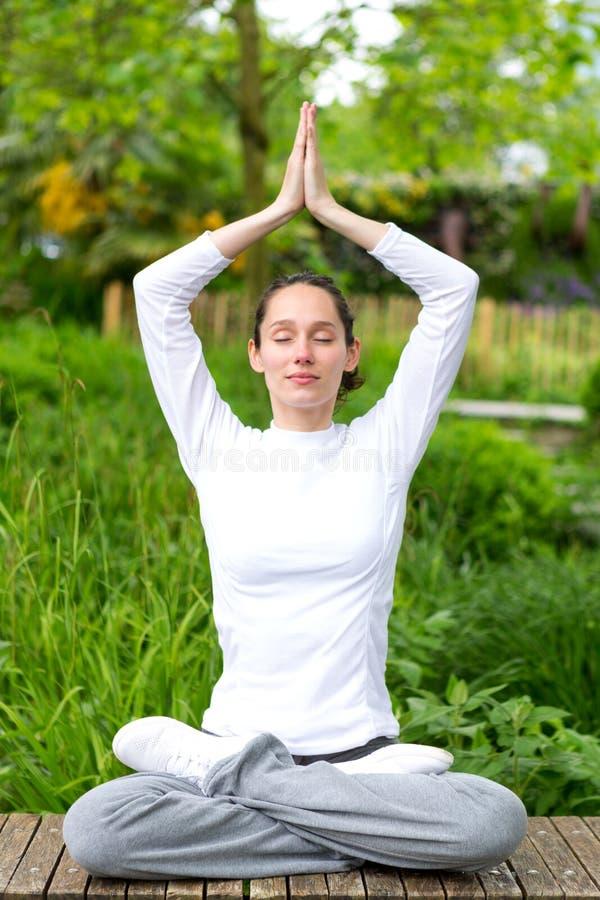 Praktiserande yoga för ung attraktiv kvinna i en parkera royaltyfria foton