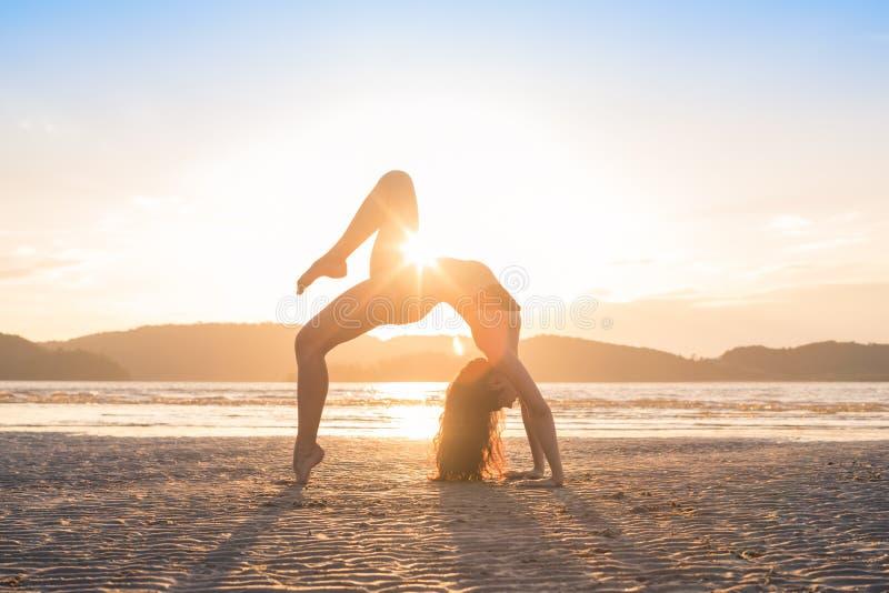 Praktiserande yoga för ung flicka på stranden på solnedgången, härlig sjösida för meditation för kvinnasommarsemester arkivbilder