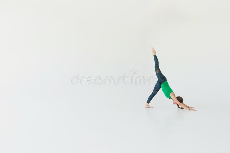 Praktiserande yoga för ung härlig kvinna i en studio Isolerat på vit minimaalism fotografering för bildbyråer