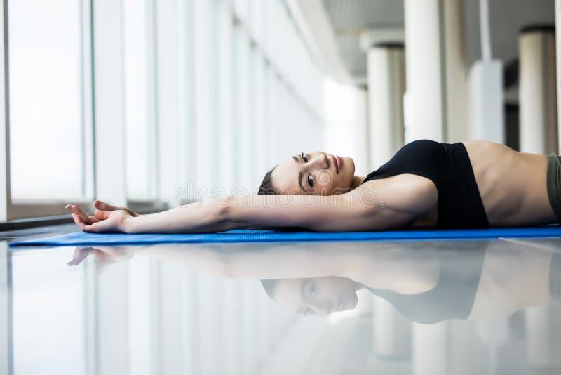 Praktiserande yoga för ung härlig kvinna med panorama- fönster i bakgrunden svart isolerad begreppsfrihet Lugn och kopplar av, kv arkivfoto