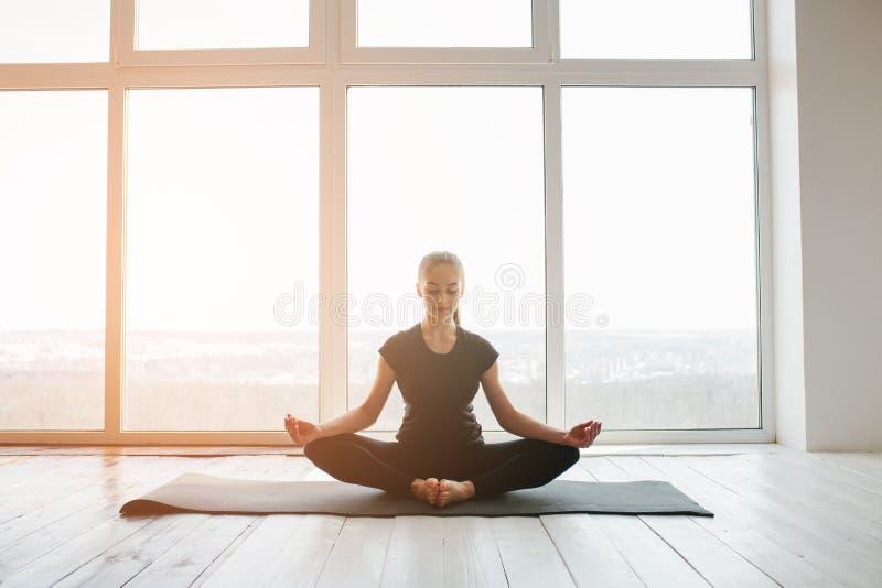 Praktiserande yoga för ung härlig kvinna och gymnastiskt Wellnessbegrepp Grupper i enkla sportar royaltyfri bild