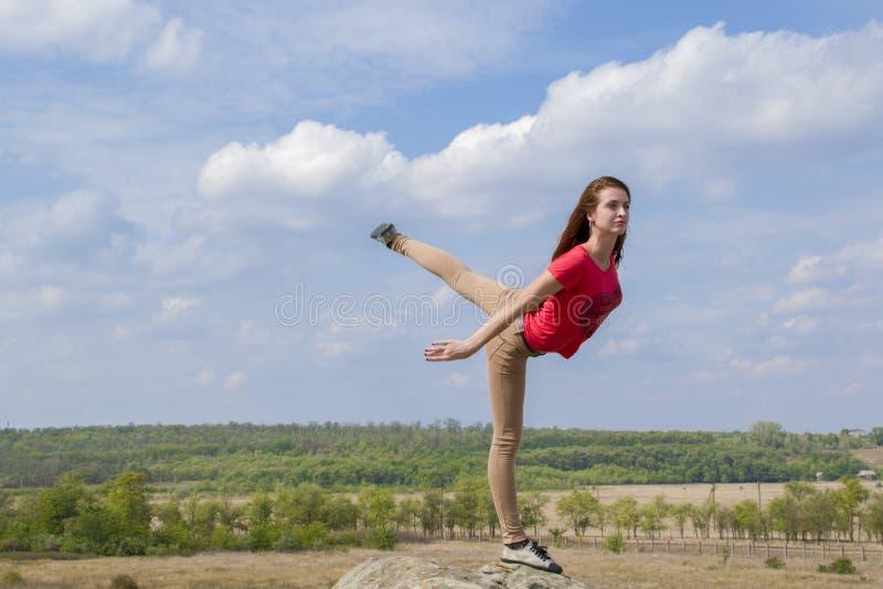 Praktiserande yoga för ung kvinna i bergen royaltyfria bilder