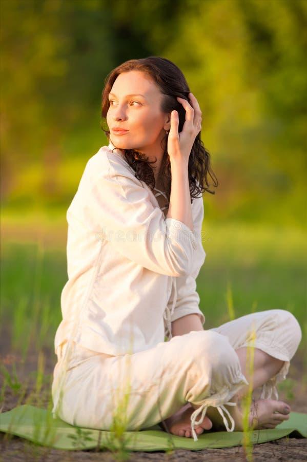Praktiserande yoga för ung kvinna på den near stranden för gräsmatta royaltyfria foton