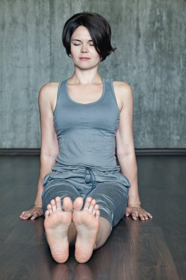 Praktiserande yoga för ung kvinna på en bakgrund av den gråa betongväggen royaltyfria foton