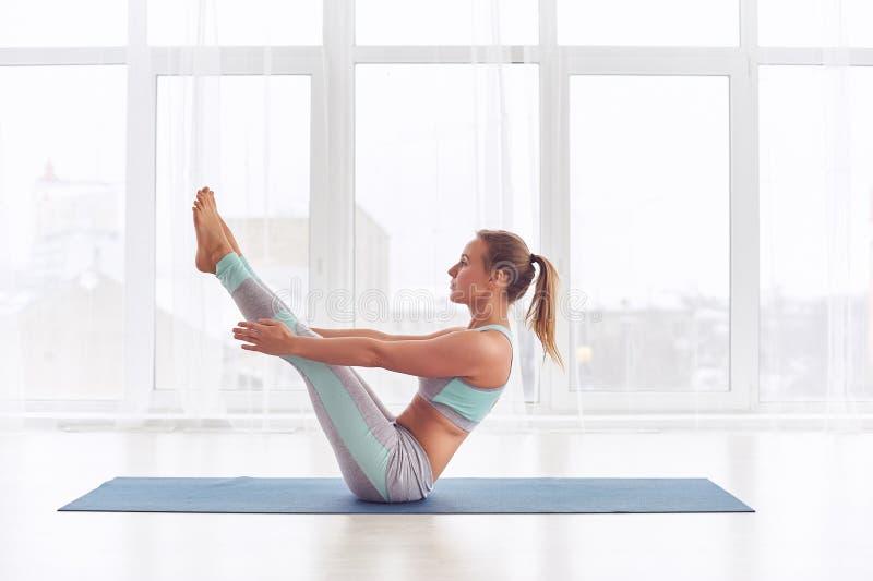 Praktiserande yoga för ung kvinna som sitter i den Paripurna Navasana övningen på yogastudion fotografering för bildbyråer