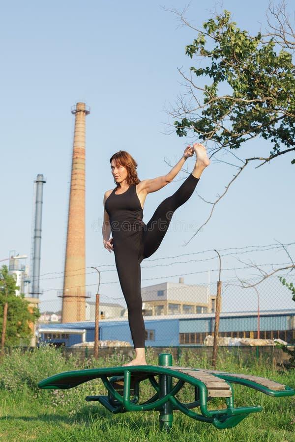 Praktiserande yoga för ung kvinna utomhus arkivfoto