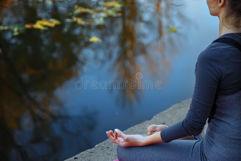 Praktiserande yoga för ung kvinna utomhus Kvinnlign mediterar utomhus- i framdel av den härliga höstnaturen royaltyfri fotografi