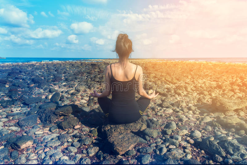 Praktiserande yoga för ung sund kvinna på stranden royaltyfri foto