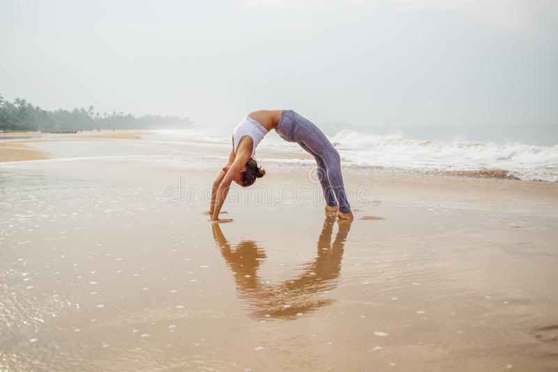 Praktiserande yoga f?r Caucasian kvinna p? kusten av v?ndkretshavet royaltyfria bilder