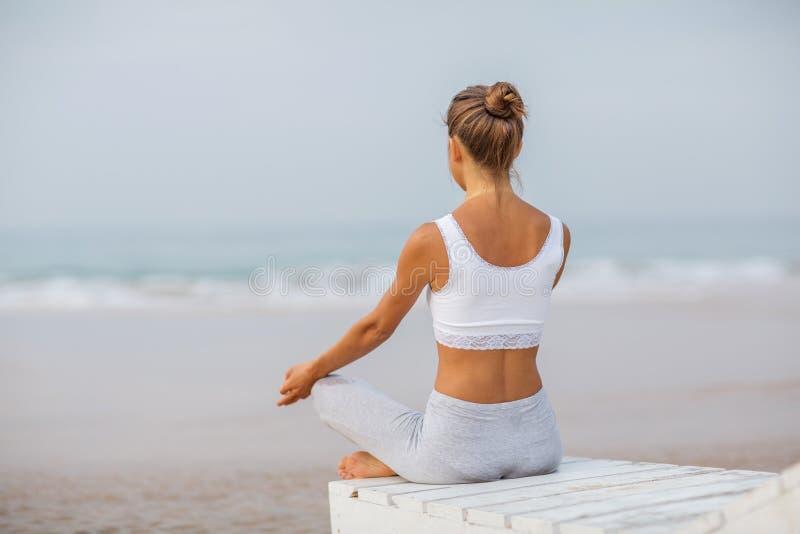 Praktiserande yoga f?r Caucasian kvinna p? kusten av v?ndkretshavet royaltyfri foto