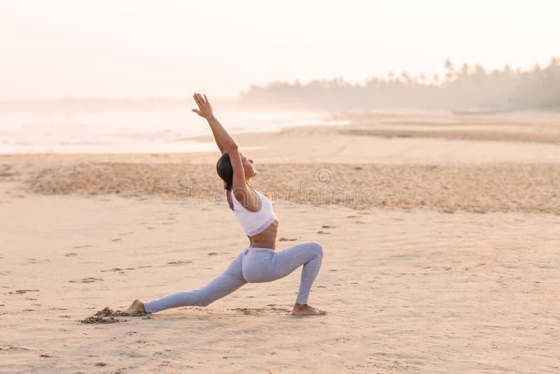 Praktiserande yoga f?r Caucasian kvinna p? kusten av v?ndkretshavet arkivfoton