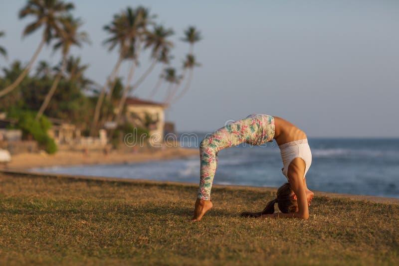 Praktiserande yoga f?r Caucasian kvinna p? kusten av v?ndkretshavet royaltyfria foton