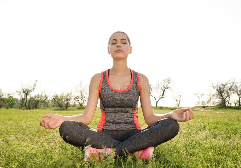 Praktiserande yoga f?r ung kvinna utomhus fotografering för bildbyråer
