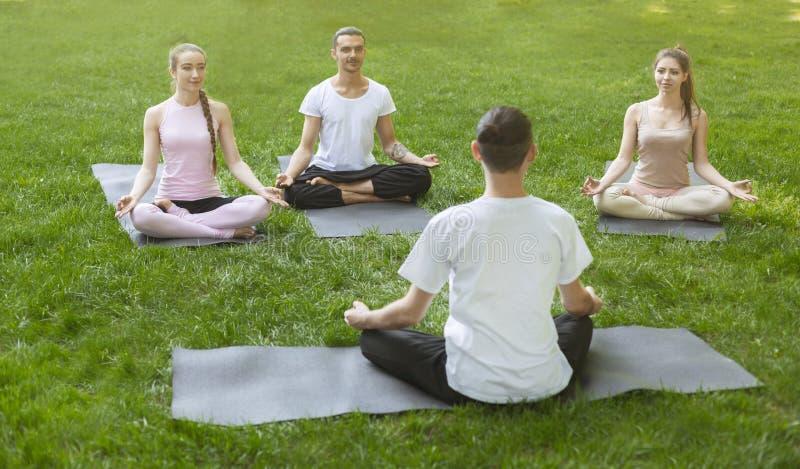 Praktiserande yogakurs för ungt sportigt folk med instruktören royaltyfria foton