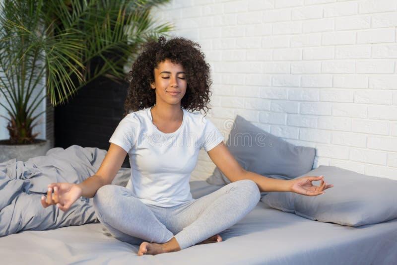 Praktiserande yogameditation för ung kvinna på hennes säng royaltyfria bilder