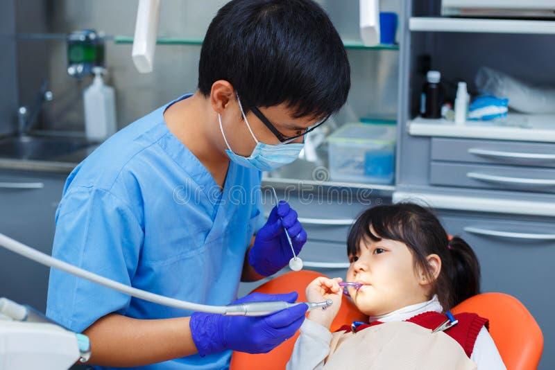 Praktizierender Zahnarzt Behandeln Sie und sein junger Patient, der nicht Angst hat stockfotos