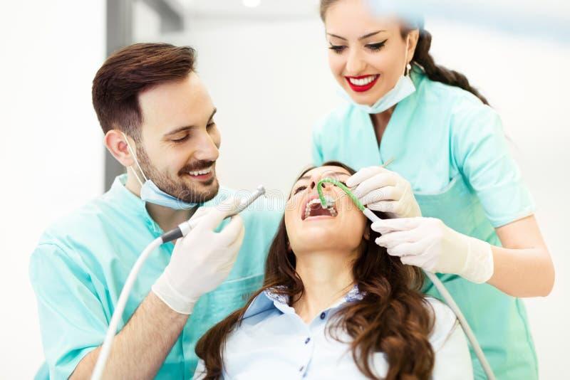 Praktizierender Zahnarzt Junges weibliches geduldiges Besuchszahnarztbüro stockbild