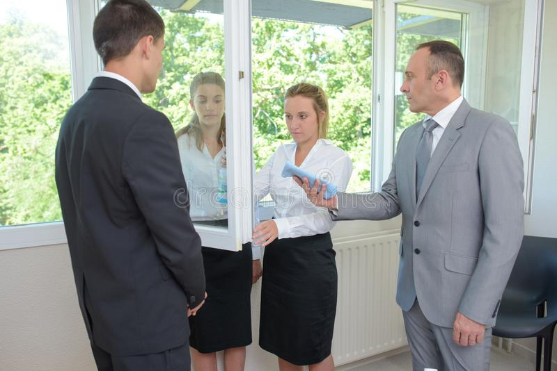 Praktykanta cleaning lustro pod nadzorem obraz royalty free