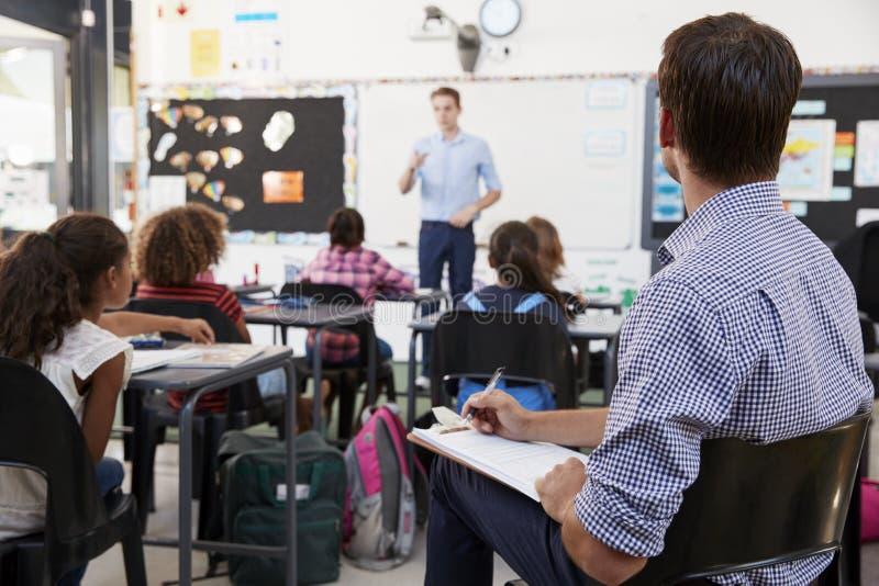 Praktykanta nauczyciela uczenie jak uczy podstawowych uczni obraz stock