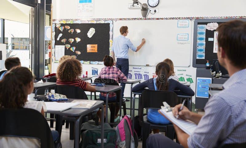 Praktykanta nauczyciela uczenie jak uczy podstawowych uczni fotografia royalty free