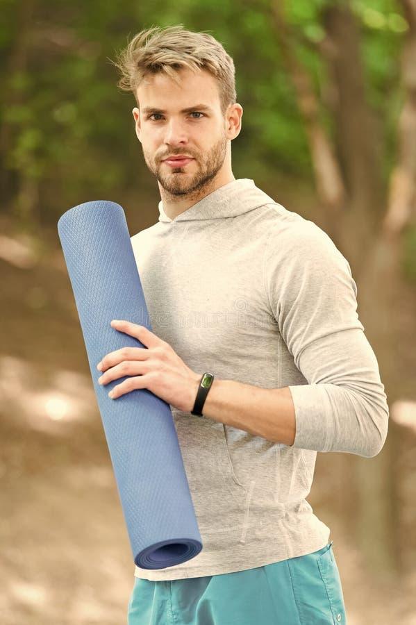 Praktyki joga w parku Atleta zawsze rozci?ga po treningu Sportowiec niesie sprawno?ci fizycznej mat? dla plenerowego szkolenia fotografia royalty free