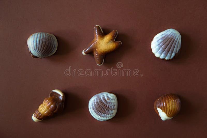 Praline assortite del cioccolato su fondo marrone fotografia stock