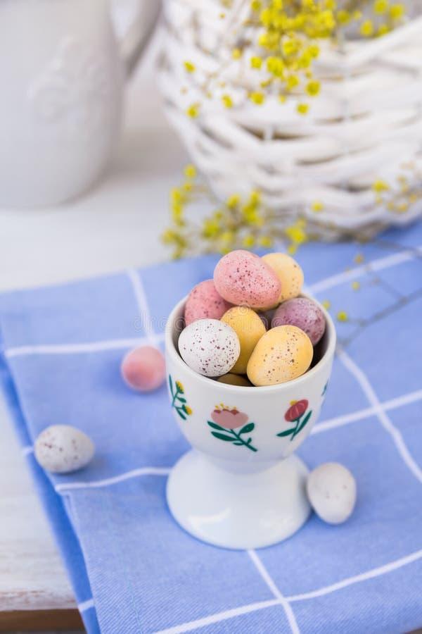 Praline färbte Ostereier in der keramischen Schale auf blauer karierter Serviette, Korb mit Blumen lizenzfreies stockfoto